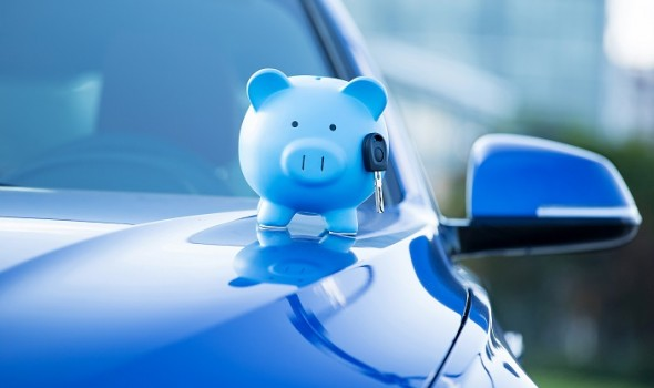 Closeup cropped image blue new car with piggy bank and key on hood, isolated outside corporate building. Dealership offering credit line finance services. Lease, automobile purchase, financing concept