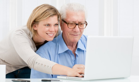 woman helps elderly man with computer