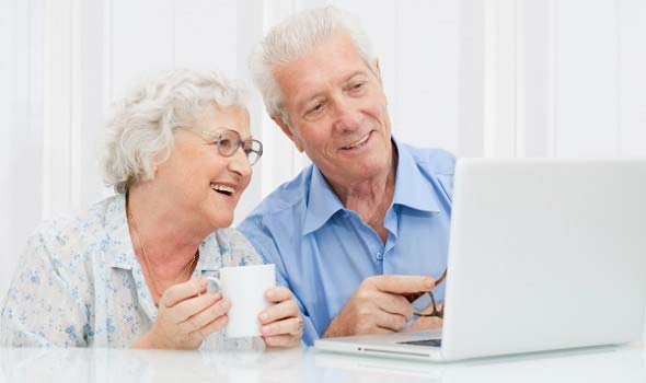 elderly couple with laptop computer