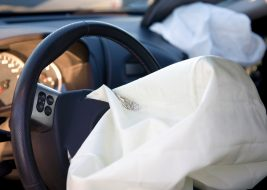 Interior view of 2 deployed airbags, view from drivers side with focus on first airbag and steering. Photographed in natural daylight, shortly after a actual car accident.