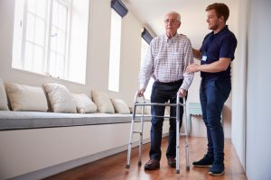 Senior woman using a walking frame with male nurse at home