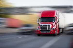 Bright red modern big rig semi truck with semi trailer move with cargo on the highway